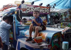 The owner/driver of the jeepney was totally at ease with me posing my son on his vehicle. I don't recommend trying this with a London cabbie.