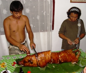 Lechon baboy served up on a bed of banana leaves. The queue for crackling forms